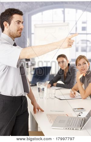 Young man presenting in meeting room, pointing, audience listening.?