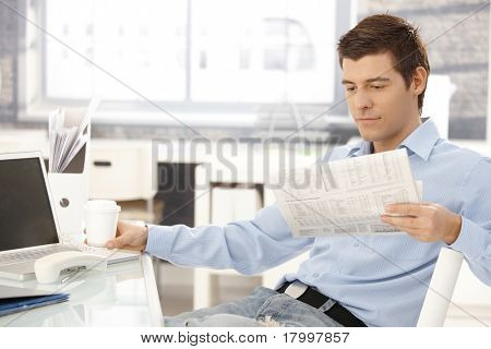 Businessman taking break in office, reading newspaper, having coffee, putting phone aside.?