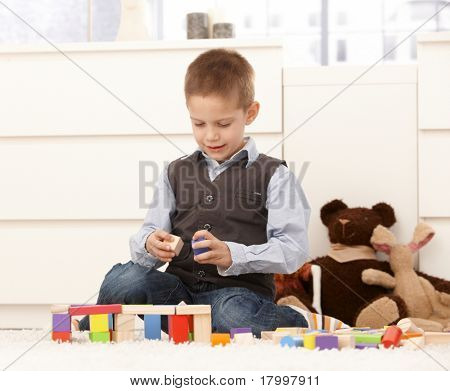 5 year old kid playing with toys on floor, smiling.?