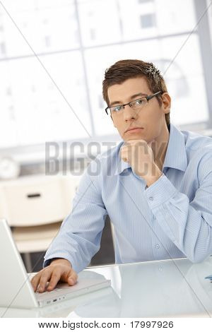 Portrait of thinking businessman sitting in office with laptop computer, looking at camera.?
