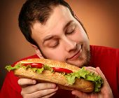funny guy eating hamburger on red background