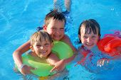 pic of swimming pool family  - Three happy children use flotation devices in a swimming pool - JPG