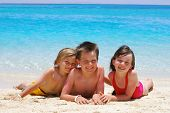 stock photo of children beach  - Three children laying in the sand at the water - JPG