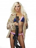 Beautiful blond lingerie model wearing army camo flak jacket while holding weapon