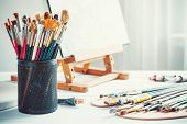 Artistic Equipment: Easel, Paint Brushes, Tubes Of Paint, Palette And Paintings On Work Table In A A poster
