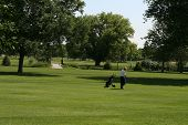 image of foursome  - A man with his golf bag walking the golf course - JPG