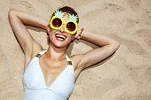 Smiling Woman In Swimsuit And Pineapple Glasses Laying On Sand poster