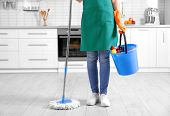 Woman holding mop and bucket with cleaning agents at home poster