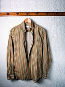stock photo of clothes hanger  - Only one striped shirt on a hanger in the wardrobe - JPG