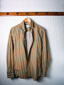 picture of clothes hanger  - Only one striped shirt on a hanger in the wardrobe - JPG