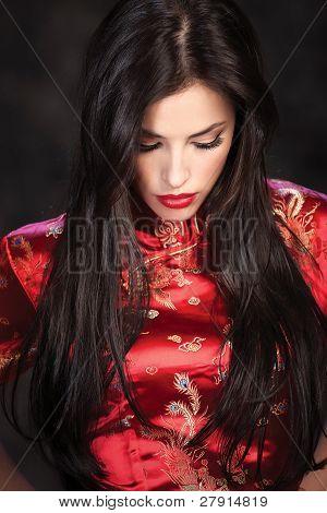 Woman In Red Cheongsam On Dark Background