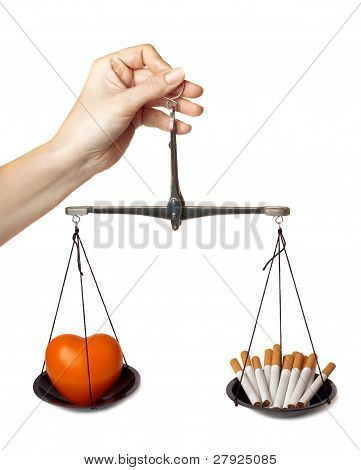Woman's Hand Holds The Scales With Orange Heart And Cigarettes.