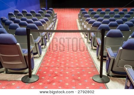 Empty Cinema Auditorium With Black Cordon With Blue Walls