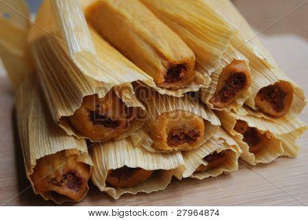 Chicken tamales in a stack on a cutting board
