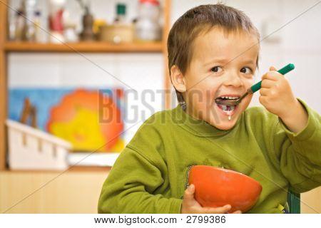 Niño feliz desayunando - cereales y leche