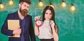 Man With Beard Hold Book And Sexy Girl Teacher Holds Alarm Clock, Chalkboard On Background. School R poster