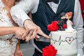 Bride And Groom Cut Wedding Cake With Red Roses, Heartbeat Rate And Figurines In Restaurant. Close U poster