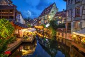 Colmar, France. Half-timbered Houses And Verandas Of Restaurants Reflecting In The Water At Dusk In  poster