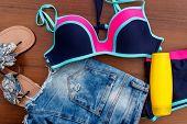 Set Of Beachwear On Wooden Background. Sunscreen, Swimsuit, Jean  Shorts And Flip-flops. Summer Holi poster
