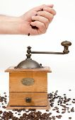 picture of wooden box from coffee mill  - Hand pouring coffee beans over a vintage grinder mill photographed over a white background - JPG