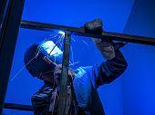 Welder Worker Performs Jump Welding. Worker Welder Performs Arc-welding Process Of Metal Structures. poster