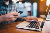 Man's Use Credit Card And Laptop For Shopping At Coffee Shop. Online Shopping, Online Payment. poster