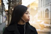 Profile Portrait Of Long Hair African 20s Teenager Woman With White Earphone And Black Coat On Sunli poster