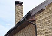 Rain Gutter Pipe System. Close Up On Brick House With Roof Tiles And Plastic Roof Gutter Pipes Drain poster
