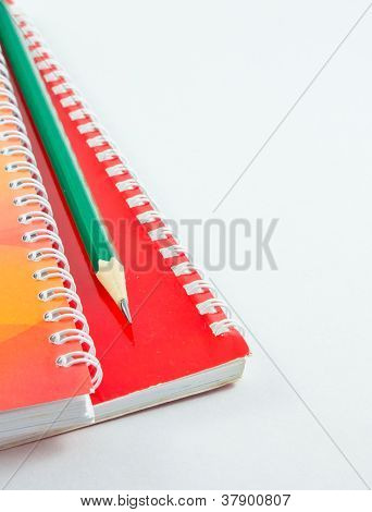 Pencil On The Red Cover Notepad Isolated With White Background