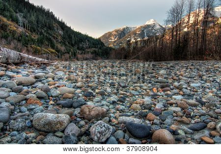 Field Of Natural Stones With Mountains