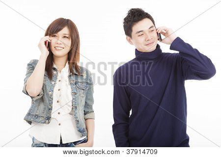 Pareja joven hablando por teléfono móvil aislado en blanco
