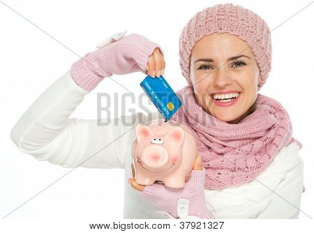 Happy Woman In Knit Winter Clothing Putting Credit Card In Piggy Bank