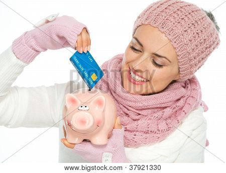 Smiling Woman In Knit Scarf, Hat And Mittens Putting Credit Card In Piggy Bank