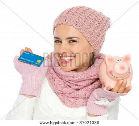 Smiling Woman In Knit Winter Clothing Holding Credit Card And Piggy Bank