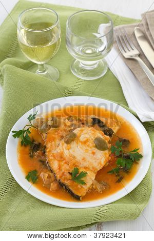 Fish In Sauce On The Plate And Glass Of White Wine