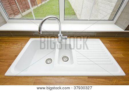 White ceramic kitchen sink with solid wooden worktop