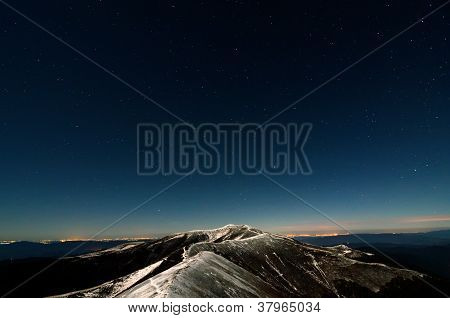 Glittering Stars Above Snowy Autumn Mountain Ridge