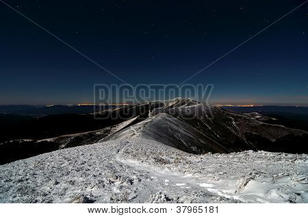 Moon Shining Over Snowy Path Over The Ridges