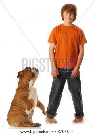 Teen Boy Standing With Bulldog Begging