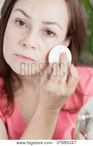 latin woman using make up