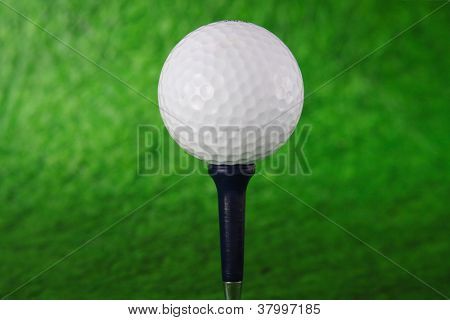 Golf Ball On Tee Over A Blurred Green
