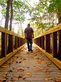 pic of walking away  - A photo of a man walking across a bridge in the middle of autumn - JPG
