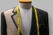 stock photo of stitches  - Unfinished black jacket with white thread stitches and yellow measuring tape - JPG