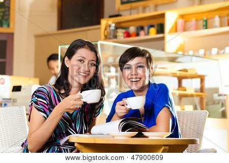 Asian female friends enjoying her leisure time in a cafe, drinking coffee or cappuccino and talking about some things