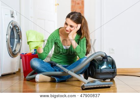 Young woman cleaning at home, she has a cleaning day and using a vacuum cleaner cleaning products and a bucket but she does not feel like it