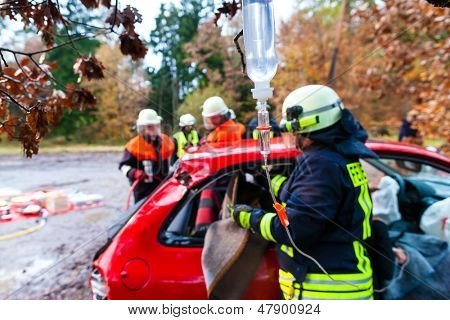 Accident - Fire brigade rescues accident Victim of a car using a hydraulic rescue tool and giving a first aid infusion