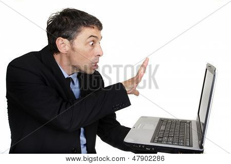 Businessman casting a spell on his laptop holding it in one hand while gesturing with his splayed hand at the screen with a look of intense amazement