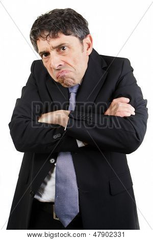 Unhappy businessman standing with his arms folded grimacing and glowering at the camera with a sullen expression, isolated on white