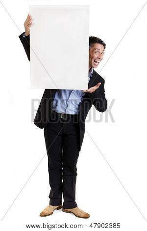 Businessman with a blank white sign peering around the side with a cheeky grin endorsing the text or advertisement to be placed on the copyspace