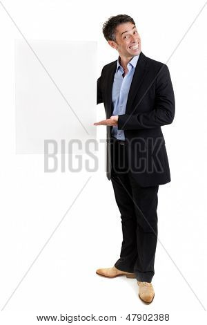 Salesman with a blank white rectangular placard with copyspace for your text or advertisement holding it to the side with a broad smile of endorsement while pointing to it